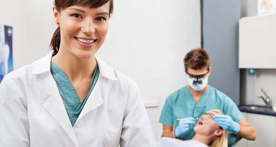 female dentist with male dentist examining patient in background