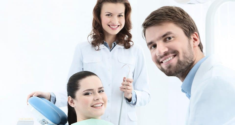 female patient smiling with a male and female dentists also smiling