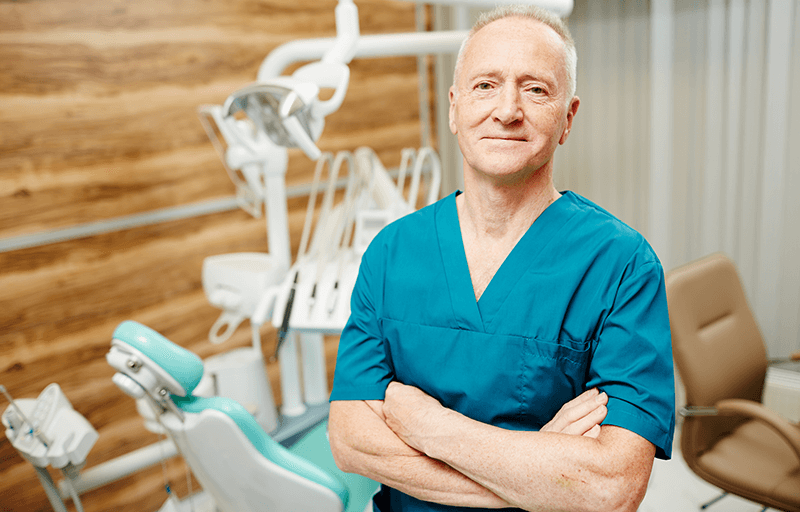 older male dentist standing with arms crossed