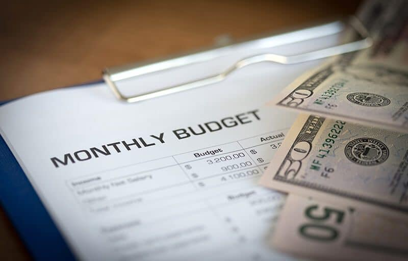 monthly budget with a stack of cash