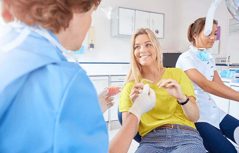 two female dentists with a female patient holding a mouth guard