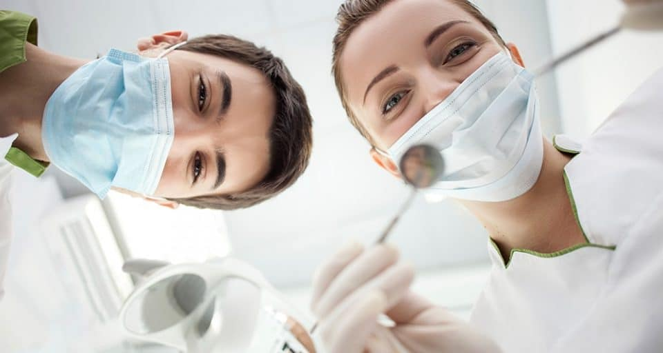 young female and male dentist with surgical masks and dental instruments